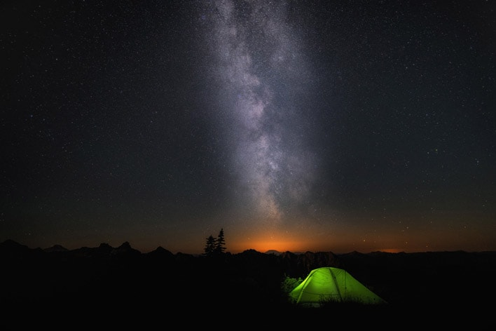 Card image with a photo of a tent in middle of a starry night.