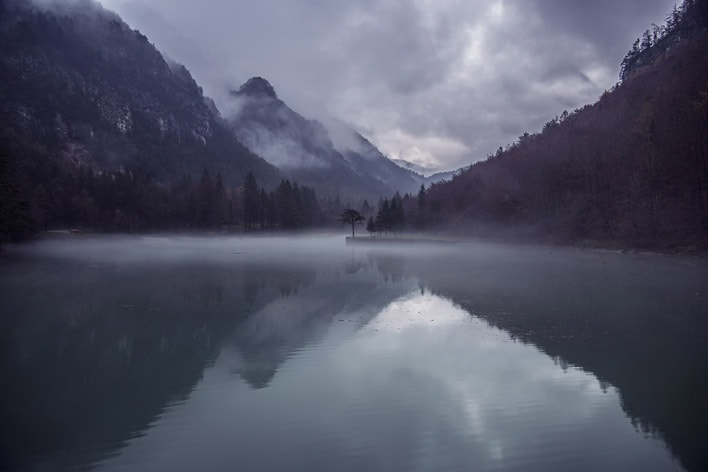 Card image of misty mountains over a lake.
