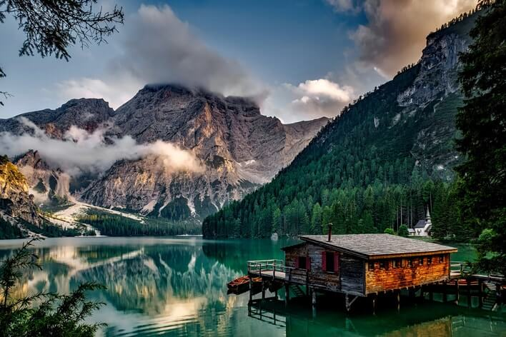 Cottage on a lake surrounded by mountains.